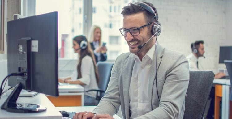 Handsome technical support agent using desktop computer in office as an image for a piece on how to contact VRBO customer service