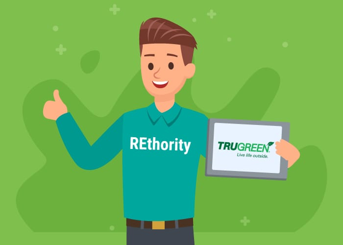Man in a REthority shirt holding a tablet that has the Trugreen logo on it