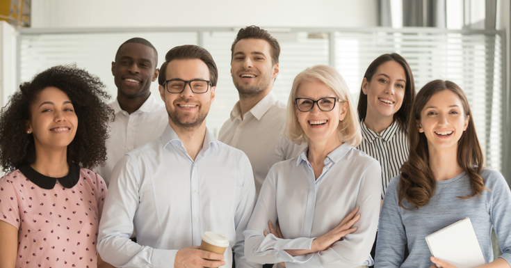 As an image for a piece on what is a condo association, Smiling multiethnic employees standing looking at camera making team picture in office together, happy diverse work group or department laugh posing for photo at workplace, show unity