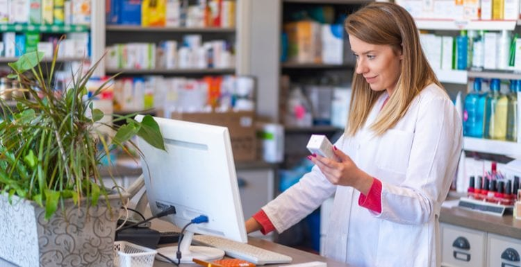 As the featured image for a piece on Costco Pharmacy, Female pharmacist working in chemist shop or pharmacy. Pharmacist using the computer at the pharmacy. Portrait of young female pharmacist holding medication while using computer at pharmacy counter