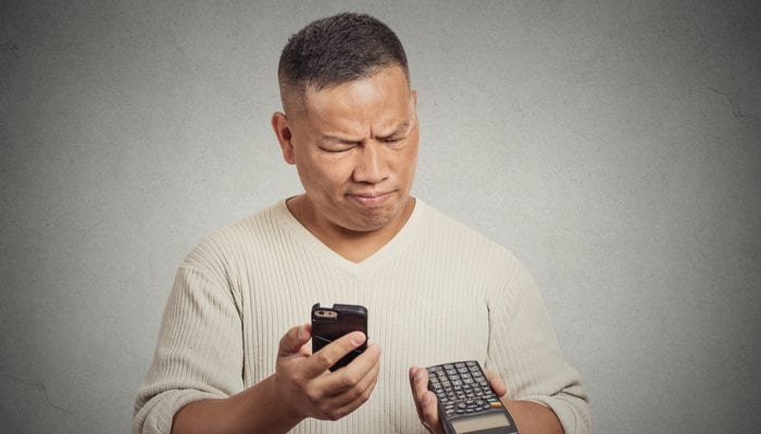 Confused man looking at his smart phone holding calculator isolated on gray wall background as an image for a piece on what is a pocket listing
