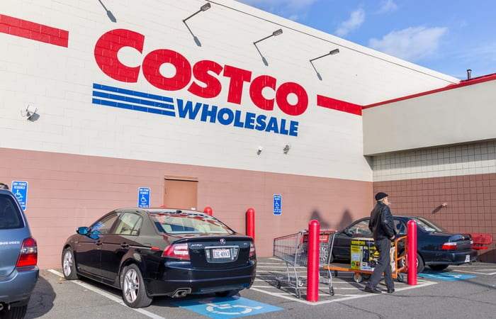 Costco return policy image featuring the front of a store with a black car