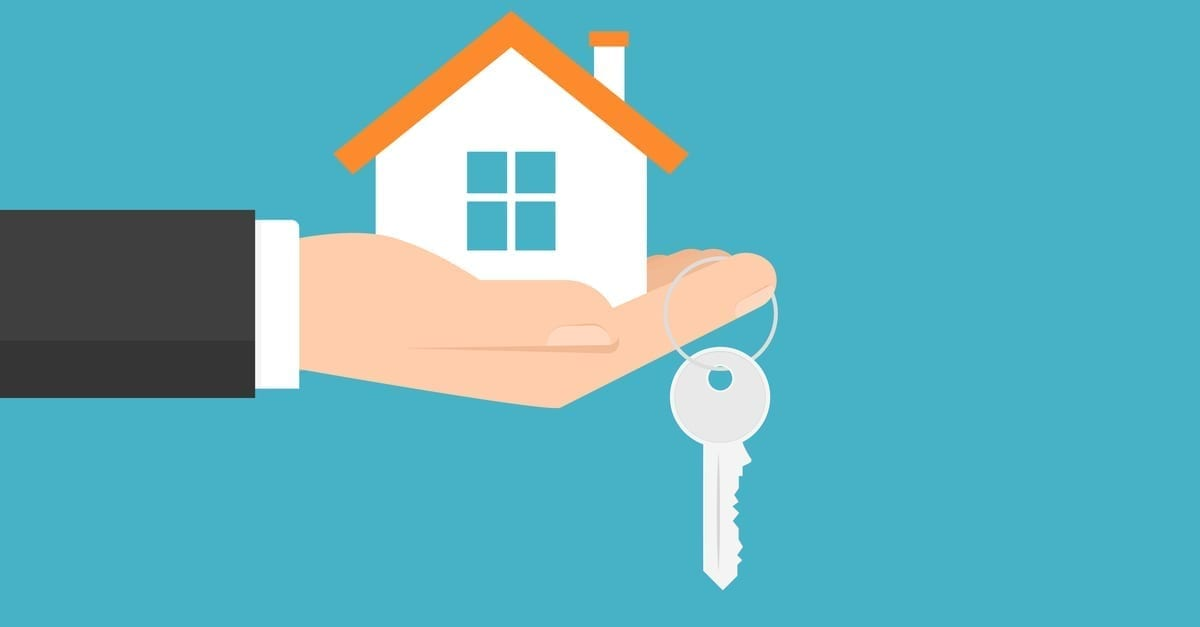 Hand holding a small home and dangling a silver key from its finger
