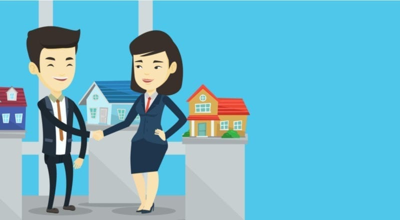 Two real estate agents standing in front of a small model home shaking hands against a generic blue background