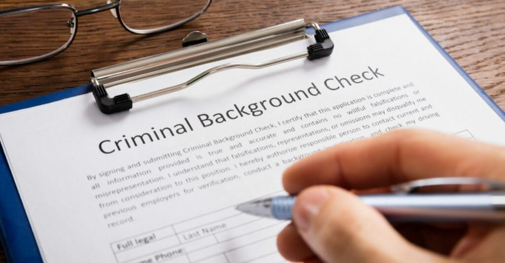 A person holding a blue pen filling out a criminal background check form with glasses sitting on the table