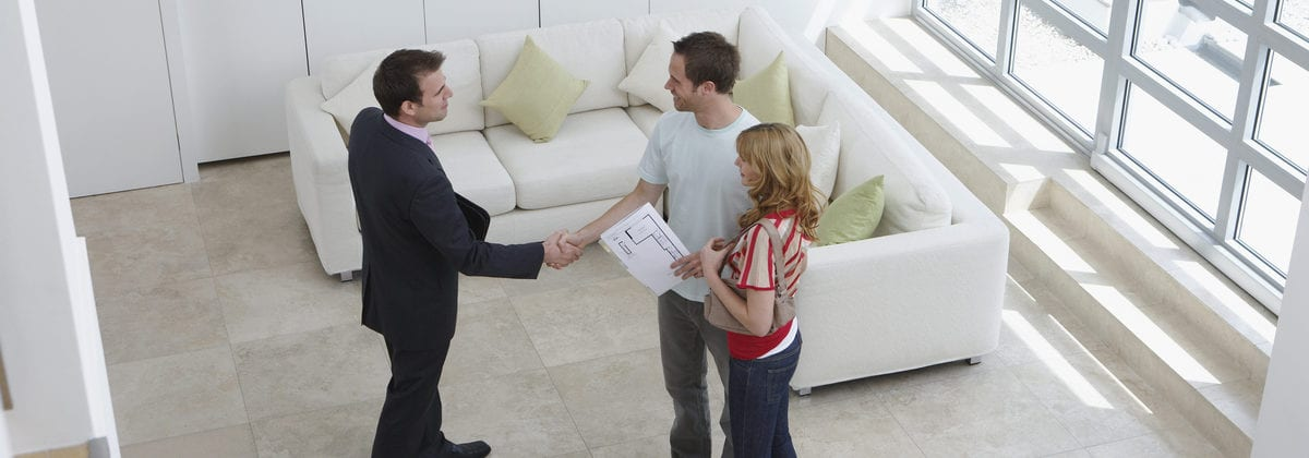Elevated view of a male real estate agent shaking hands with a man by woman in new home
