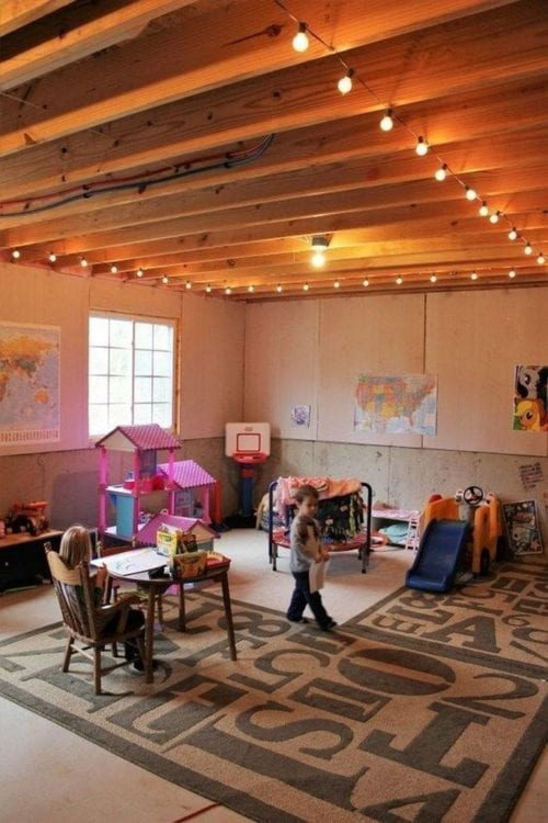 Basement with a kids flooring space using string lights and carpeting