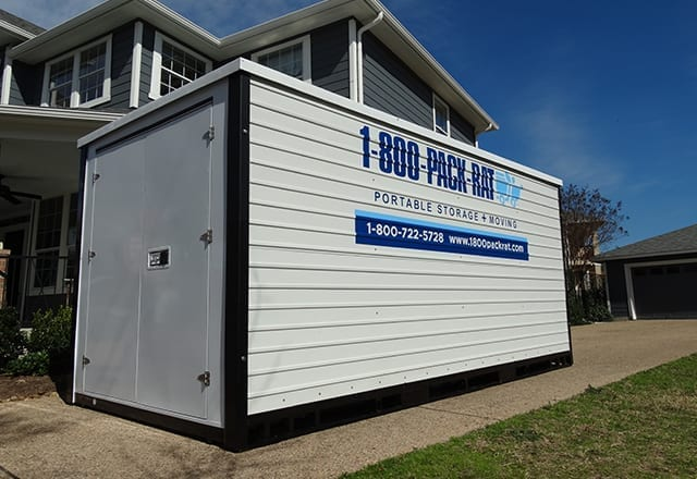 A 1-800-PACK-RAT moving container sitting in the driveway of a nice blue suburban home