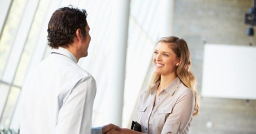 Businessman And Businesswoman Shaking Hands In Office as the result of a warm introduction