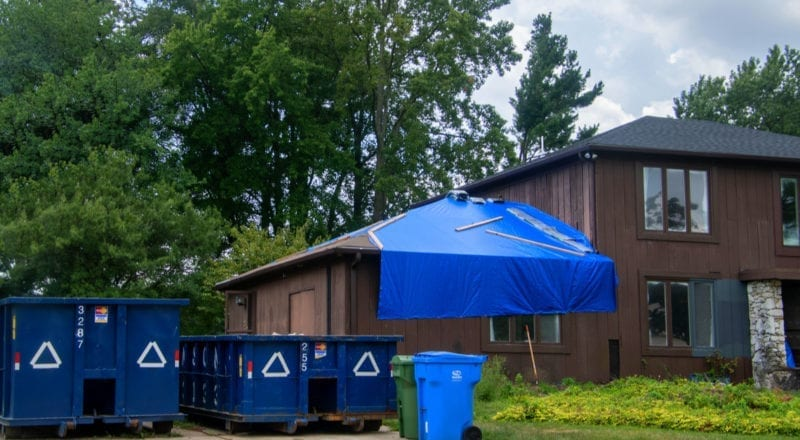 Cherry Hill, New Jersey - August 18, 2019: Large brown wooden house is seen with blue tarp over garage roof and two dumpsters in the driveway due to renovation after storm damage