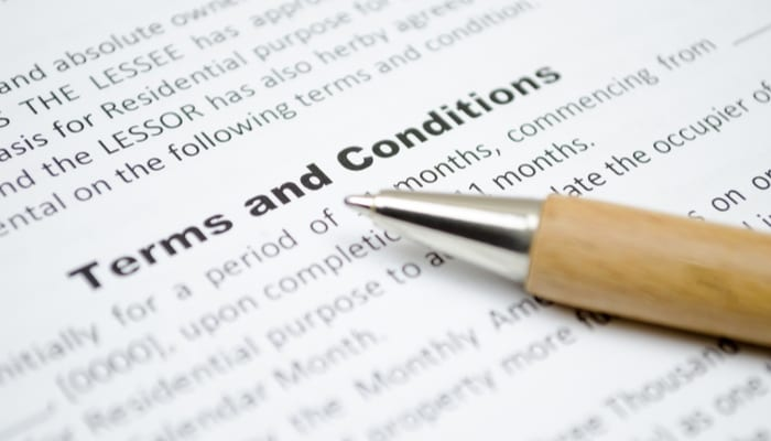 A list of terms and conditions on a contract with a pen sitting on top of the paper as the featured image for a piece on Seller Carryback