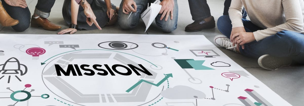 "A group of young people in business casual attire sitting around a piece of paper with the word ""mission"" on it as the featured image for a piece on real estate mission statements"