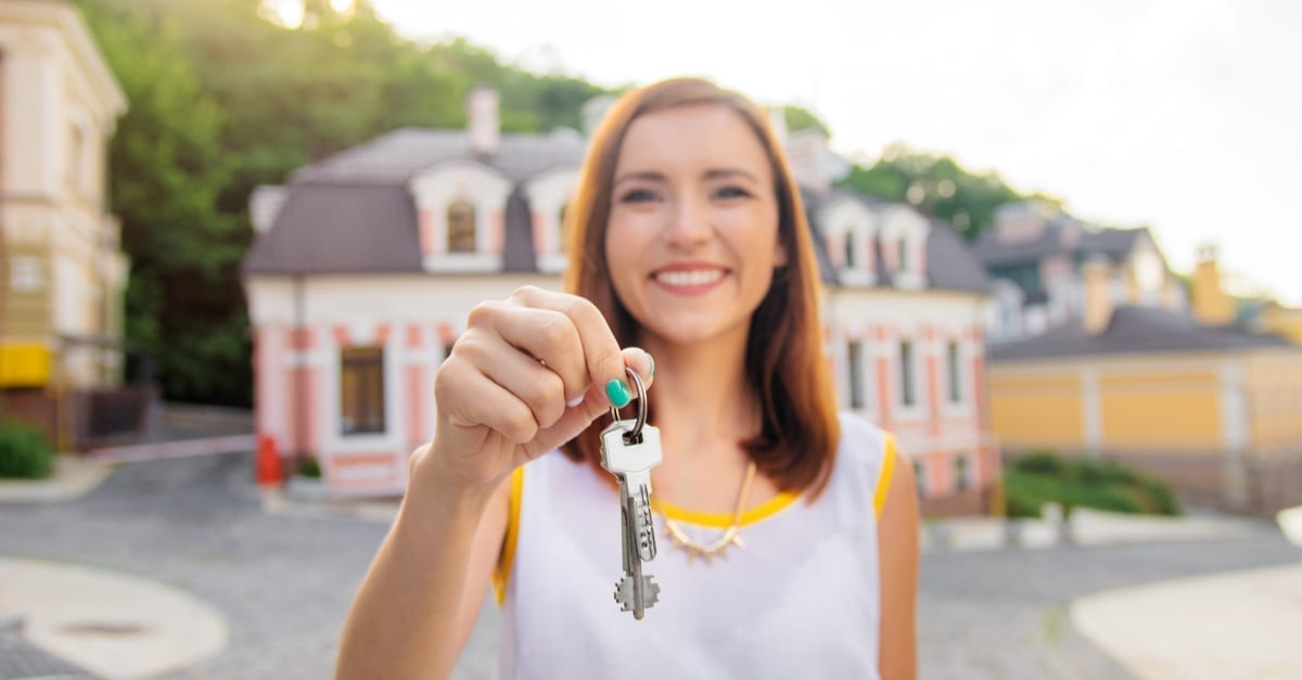 Real estate. Happy broker. Attractive young woman holding keys while standing outdoor against new house as the featured image for a piece on Showing Suite