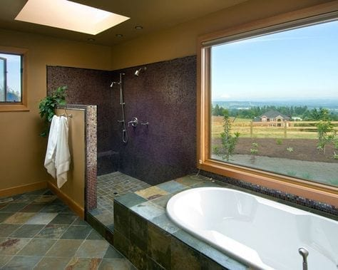 Brown slate tile bathroom with a half shower wall without door and a picture window above the tub