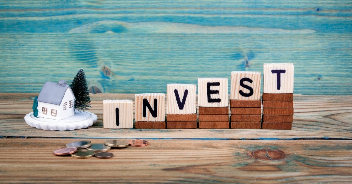 miniature model of house and wooden letter text: invest as the featured image for a piece on the BRRRR Strategy