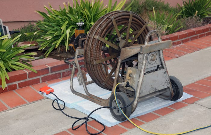 Sewer cleaning. A plumber uses a sewer snake to clean blockage in a sewer line.