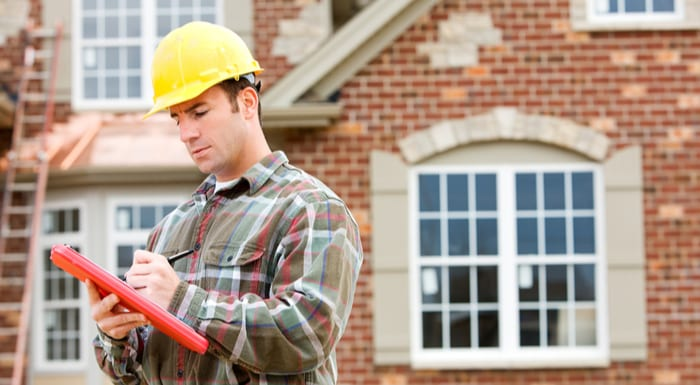 Man in a yellow hard hat stands outside of a beautiful brick home with a ladder in the back as the featured image for a piece on real estate jobs