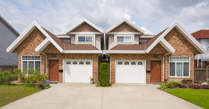 Two homes sitting next to each other with a shared driveway as the featured image for a piece on buying a duplex