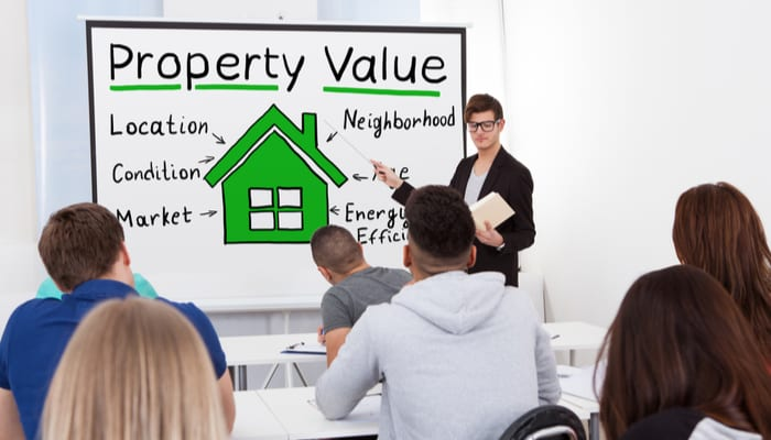 A Male Teacher Explaining The Concept Of Property Value Concept To Students In Classroom for a piece on a real estate express review