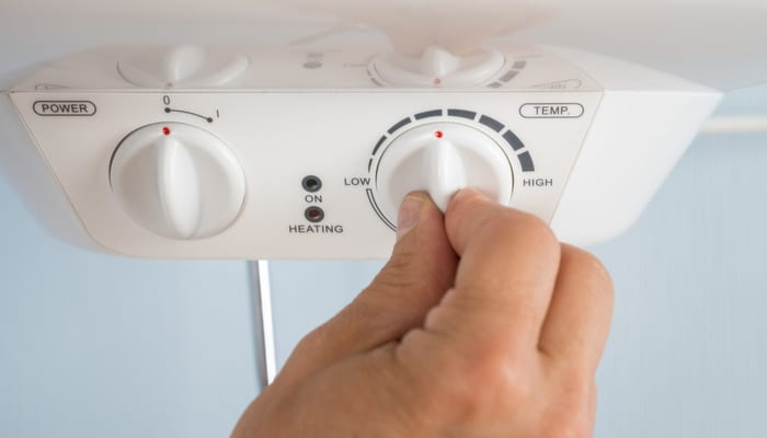 Close-up Of A Person's Hand Adjusting Temperature Of Electric Boiler