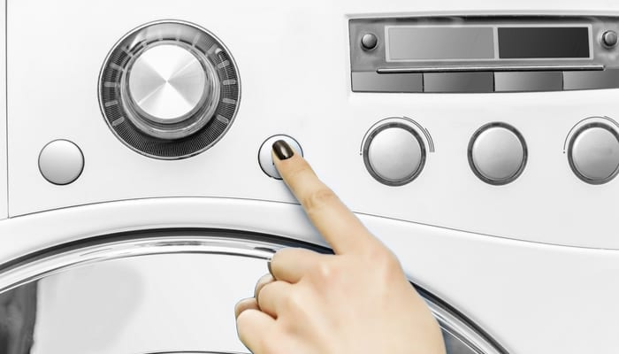 A woman's hand presses a button on the washing machine. Start the wash cycle.