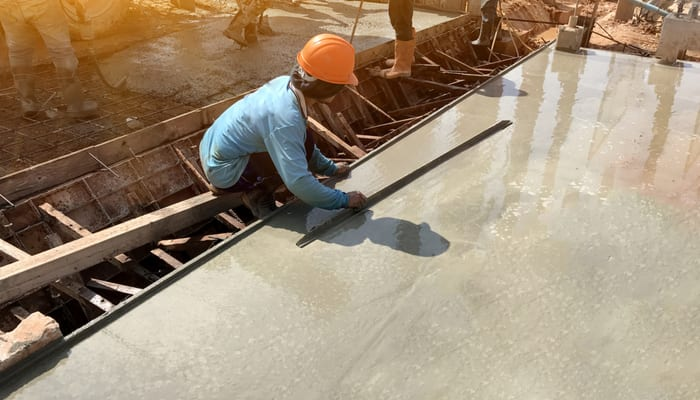 man hand spreading concrete mix with trowel in foundation. A construction worker is pouring cement and concrete,Selective focus.