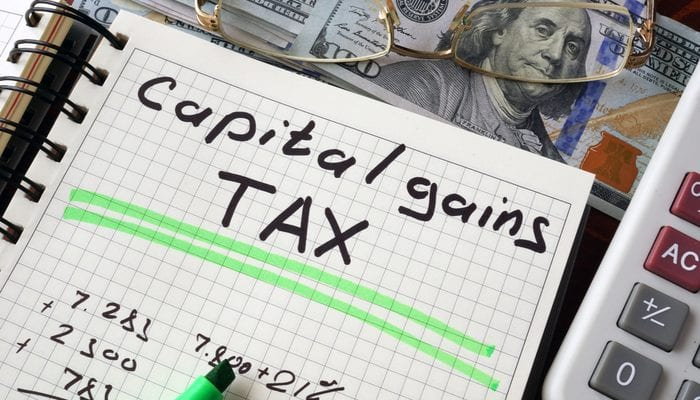 Notebook with capital gains tax sign on a table. Business concept. as an image for a piece on are home improvements tax deductible