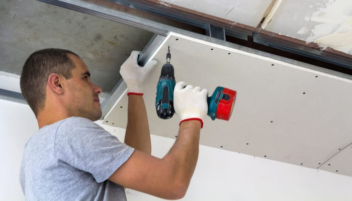 Construction worker assemble a suspended ceiling with drywall and fixing the drywall to the ceiling metal frame with screwdriver. Renovation, construction and do it yourself DIY concept.