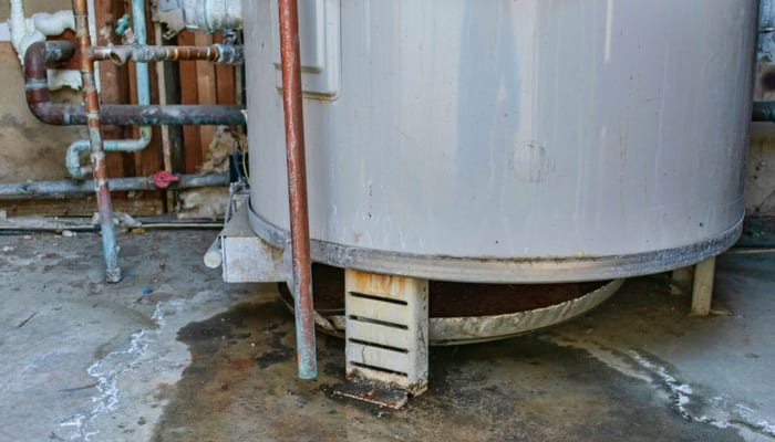 Water heater leaks from the bottom to the floor. Overflowing water heater drip pan. It is time to call a plumber service for inspection, repair or replacement