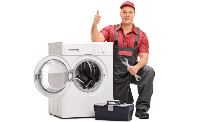 Worker repairing broken washing machine and giving thumb up isolated on white background