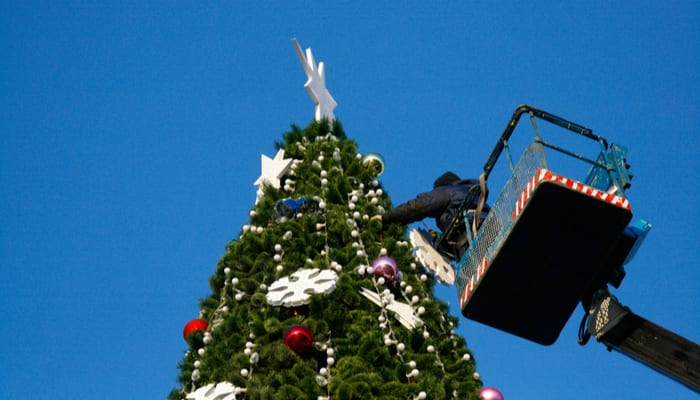 A Christmas light installer in a boom lift standing next to a Christmas tree decorating it