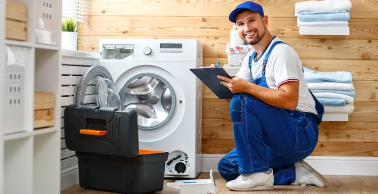 As an image for a piece on Appliance Repair Near Me, working man plumber repairs a washing machine in laundry