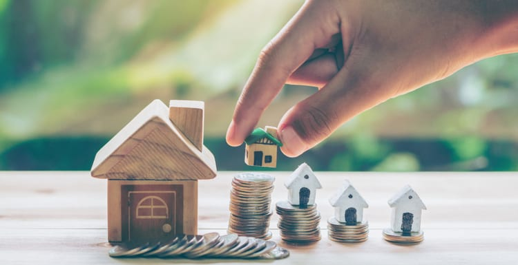 House placed on coins Men's hand is planning savings money of coins to buy a home concept concept for property ladder, mortgage and real estate investment. for saving or investment for a house to answer the question how much do property managers charge