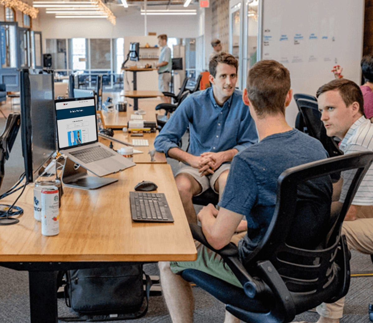 Multiple REthority employees sitting in the REthority office looking at a picture of a water heater review
