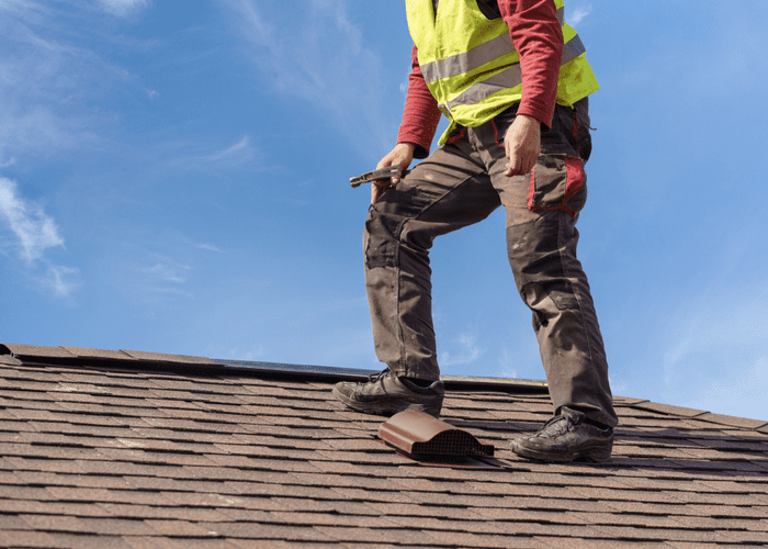 For a piece on the best roofing contractors in Omaha, a guy stands on a roof in a yellow vest against a blue sky