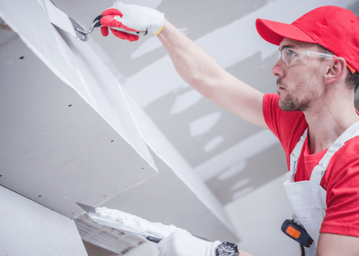 Late 30s caucasian man in a red hat and shirt mudding unfinished drywall for a piece on how much does it cost to have someone finish drywall