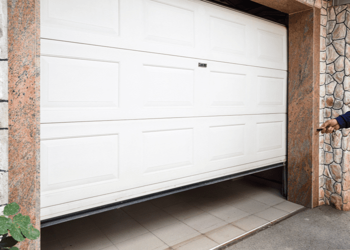 For a piece on how to align garage door sensors, a person clicking the remote while closing the white door between stones