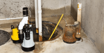 For a piece on how to install a sump pump, two new pumps sit on a concrete slab above the hole