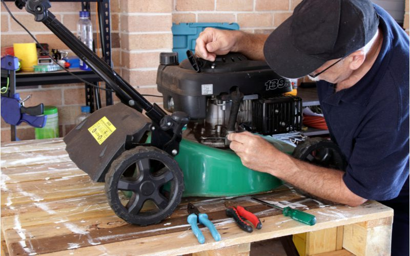 Man repairing his lawn mower with tools and adjusting the fuel line. Lawn mower won't keep running