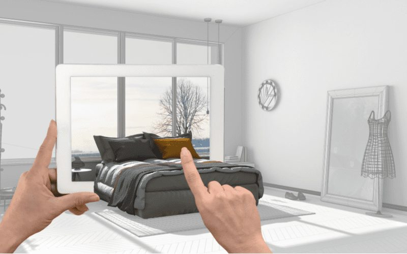 As a room design app concept, a person holds an ipad through which a virtual 3d room springs to life while she touches the pillow