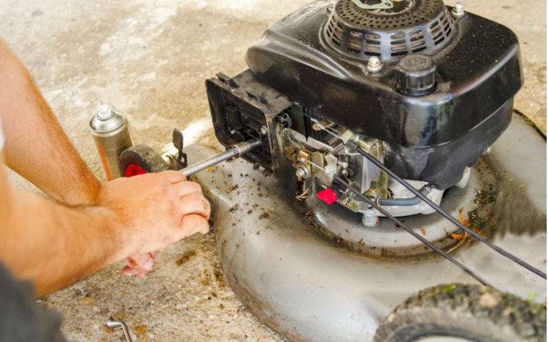 Man taking apart his lawnmower that won't keep running and attempting to clean the carb