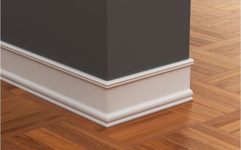 Types of crown molding featuring a baseboard below a dark grey wall