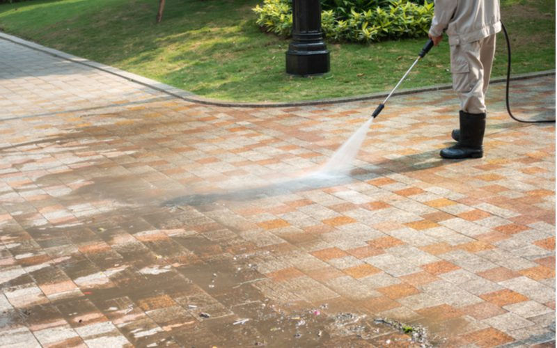Easy curb appeal idea of power washing a sidewalk to get the grime off the brick pavers