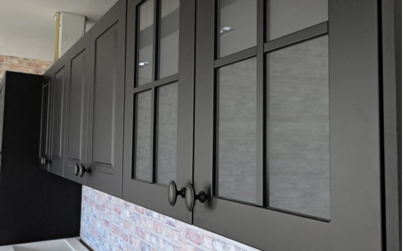 To illustrate the process of painting laminate cabinets, a number of them sit with glass doors on the front