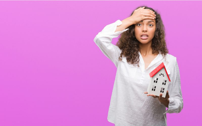 Stressed Hispanic-Afro-American woman holding her forehead and a model of a house in a purple room because she wants to know why real estate agents fail