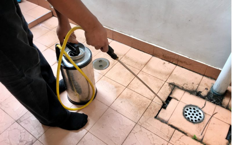 Male spraying liquid insect repellant on and around a drain