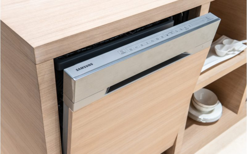 Samsung dishwasher (a brand to avoid) in a cabinet with light wooden trim