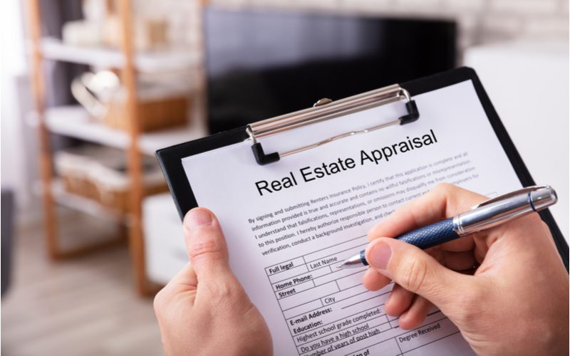 Person holding a real estate appraisal worksheet and checking boxes