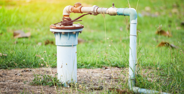 Featured image for a piece on well pump repair with a pvc pipe running to the pump into a pipe that protrudes from under ground