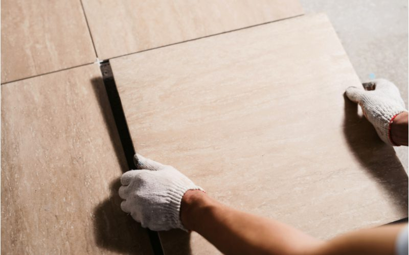Image of a piece on sanded vs unsanded grout featuring a guy laying tile before applying the grout